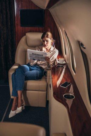 Foto de Atractiva mujer en camisa leyendo periódico negocio en avión privado - Imagen libre de derechos