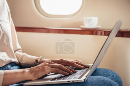 Photo for Cropped view of woman using laptop in private plane - Royalty Free Image