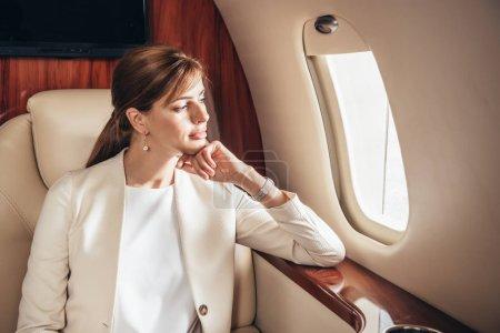 Photo pour Attractive business woman in suit looking through window in private plane - image libre de droit