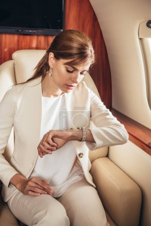 Photo pour Attractive businesswoman in suit looking at wristwatch in private plane - image libre de droit