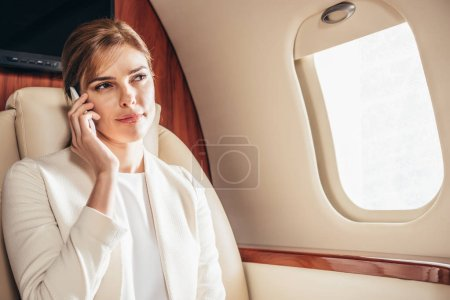 attractive businesswoman in suit talking on smartphone in private plane