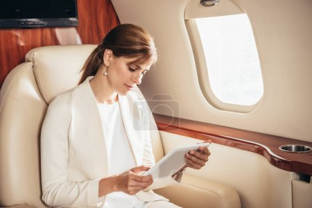 Photo for Attractive businesswoman in suit using digital tablet in private plane - Royalty Free Image