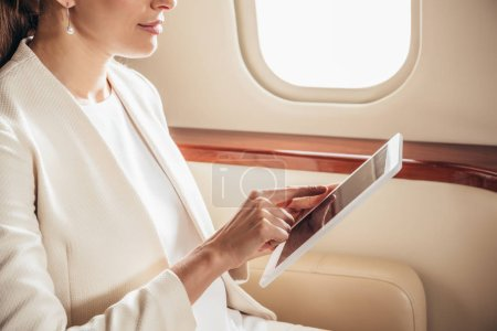 Photo pour Cropped view of businesswoman in suit using digital tablet in private plane - image libre de droit