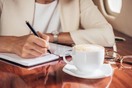Photo pour Crochet vue d'une femme d'affaires en poursuite écriture dans un carnet en privé - image libre de droit