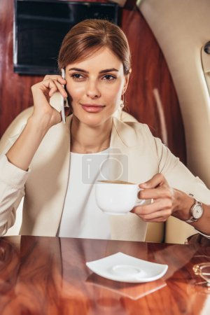attractive businesswoman in suit holding cup and talking on smartphone in private plane