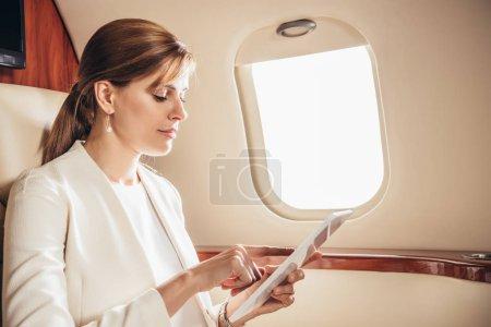 Photo pour Séduisante femme d'affaires en costume en utilisant une tablette numérique en avion privé - image libre de droit