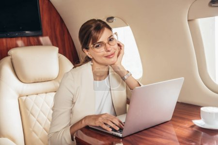 Photo pour Attractive business woman in suit with laptop looking at camera in private plane - image libre de droit