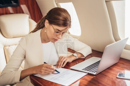 Photo for Attractive businesswoman in suit doing paperwork in private plane - Royalty Free Image