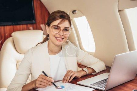 sonriente mujer de negocios en traje haciendo papeleo en avión privado