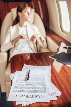 Selektive Fokussierung von Vertrag und Stift auf Holztisch im Privatflugzeug