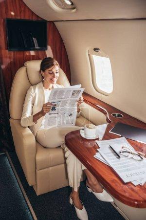 Photo pour Une femme d'affaires souriante en costume de lecture d'un journal privé - image libre de droit