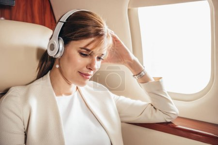 attractive businesswoman in suit listening music with headphones in private plane