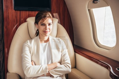 Photo pour Attractive business woman in suit with crossed arms looking at camera in private plane - image libre de droit