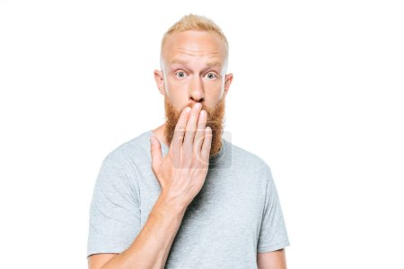 Photo for Surprised man in grey t-shirt covering mouth, isolated on white - Royalty Free Image