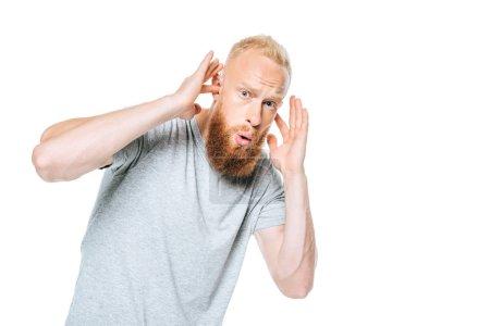 Photo pour Un homme barbu inquiet en t-shirt gris se refermant les oreilles d'un son fort, isolé sur blanc - image libre de droit
