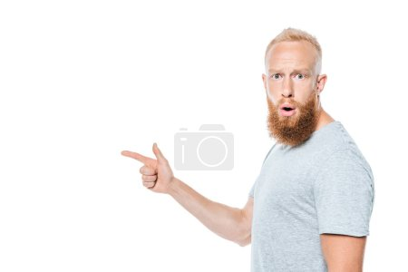 Photo for Shocked bearded man in grey t-shirt pointing isolated on white - Royalty Free Image