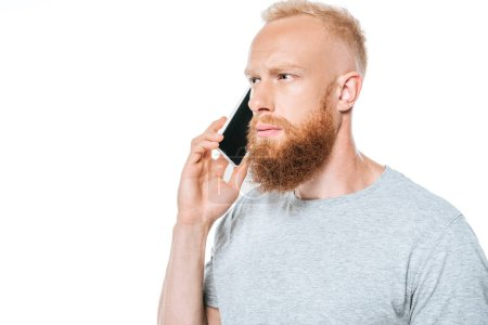 Photo for Thoughtful bearded man talking on smartphone, isolated on white - Royalty Free Image