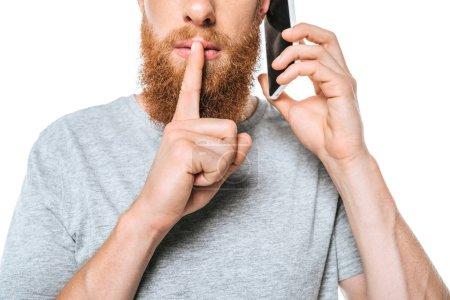 Photo pour Vue recadrée de l'homme barbu parlant sur smartphone et montrant le symbole du silence, isolé sur blanc - image libre de droit