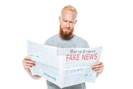 Photo pour Homme barbu sceptique lisant le journal avec de fausses nouvelles, isolé sur blanc - image libre de droit