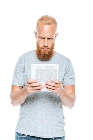 Photo pour Homme barbu grave utilisant tablette numérique, isolé sur blanc - image libre de droit