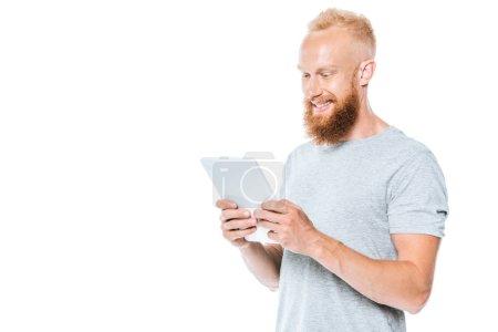 Photo pour Bel homme souriant utilisant une tablette numérique, isolé sur blanc - image libre de droit
