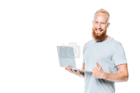 cheerful bearded man using laptop and showing thumb up, isolated on white