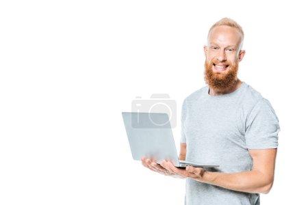 homme barbu joyeux tenant ordinateur portable, isolé sur blanc
