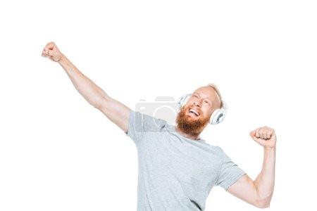 barba excitada hombre escuchando música con auriculares y bailando, aislado en blanco
