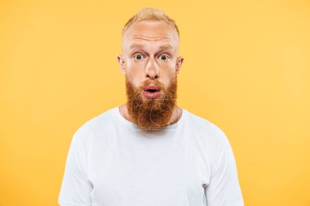 Photo for Portrait of surprised handsome bearded man looking at camera, isolated on yellow - Royalty Free Image