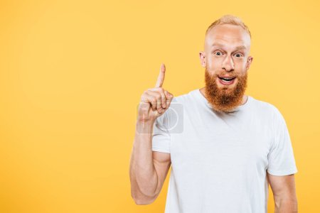portrait of excited bearded man pointing up with idea, isolated on yellow