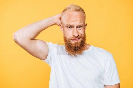 Photo pour Portrait d'un bel homme barbu confus, isolé sur jaune - image libre de droit