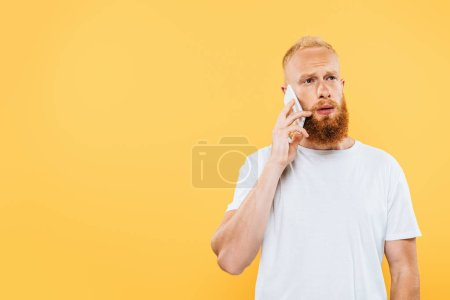 Photo for Thoughtful bearded man talking on smartphone, isolated on yellow - Royalty Free Image