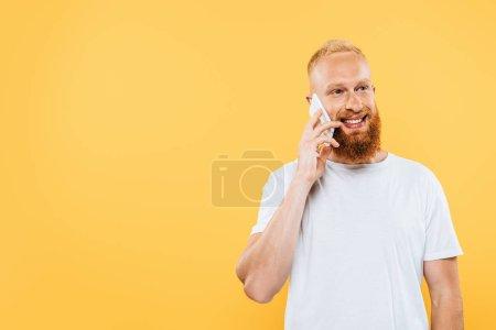 Photo pour Heureux homme barbu parler sur smartphone, isolé sur jaune - image libre de droit