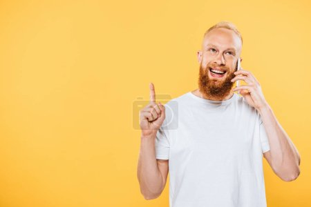smiling bearded man having idea while talking on smartphone, isolated on yellow