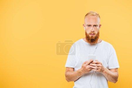 Photo pour Bel homme sérieux écoutant de la musique avec écouteurs et smartphone, isolé sur jaune - image libre de droit