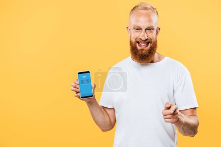 Photo for KYIV, UKRAINE - AUGUST 27, 2019: smiling bearded man presenting smartphone with Skype app and pointing at you, isolated on yellow - Royalty Free Image
