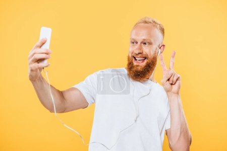 Photo pour Homme barbu heureux avec écouteurs prenant le sélecteur sur smartphone et montrant le signe de la victoire, isolé sur jaune - image libre de droit