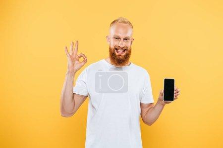 Photo pour Homme barbu souriant montrant ok signe et smartphone avec écran blanc, isolé sur jaune - image libre de droit