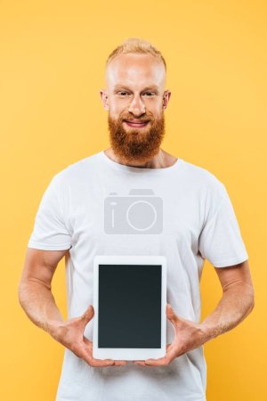 smiling bearded man showing digital tablet with blank screen, isolated on yellow