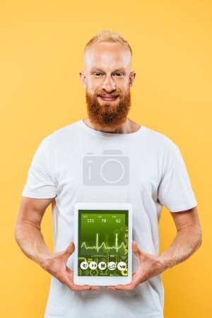 bearded man showing digital tablet with on health app screen, isolated on yellow