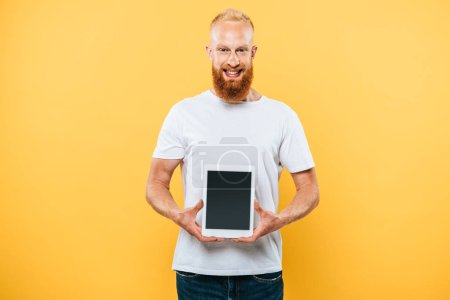 cheerful man showing digital tablet with blank screen, isolated on yellow