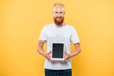 fröhlicher Mann zeigt digitales Tablet mit leerem Bildschirm, isoliert auf gelb