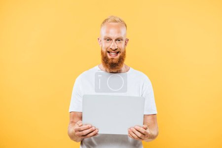 happy bearded man using laptop, isolated on yellow