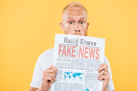 Photo for Surprised bearded man holding newspaper with fake news, isolated on yellow - Royalty Free Image
