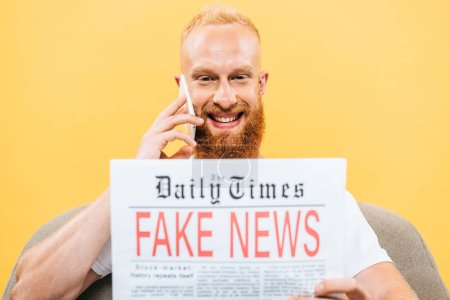 Photo for Cheerful man reading newspaper with fake news and talking on smartphone while sitting on armchair, isolated on yellow - Royalty Free Image