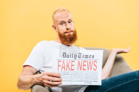 Photo for Skeptical man reading newspaper with fake news while sitting on armchair with shrug gesture, isolated on yellow - Royalty Free Image