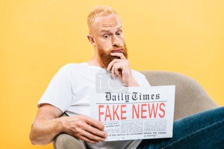 Photo pour Homme réfléchi lisant journal avec de fausses nouvelles tout en étant assis sur un fauteuil, isolé sur jaune - image libre de droit