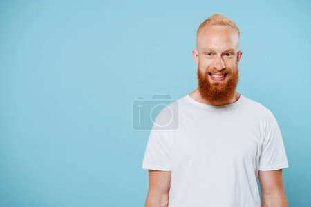 Photo for Portrait of handsome smiling bearded man in white t-shirt, isolated on blue - Royalty Free Image