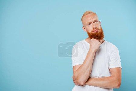 Photo for Portrait of handsome sad bearded man thinking isolated on blue - Royalty Free Image