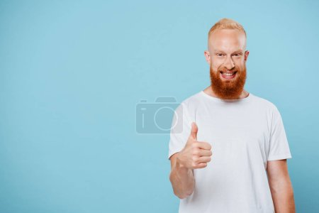 portrait of cheerful bearded man in white t-shirt showing thumb up, isolated on blue